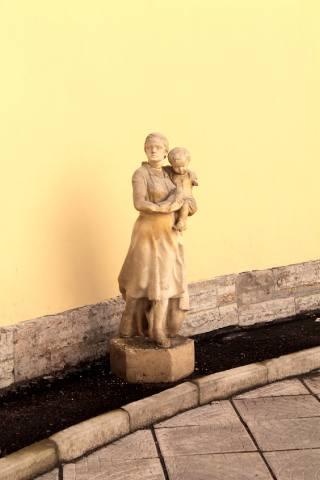 Скульптура Женщина с ребёнком во дворе круглого дома…