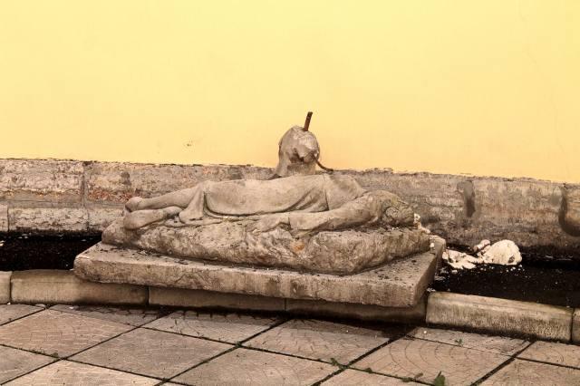 Фрагменты лежачей статуи во дворе дома-кольцо